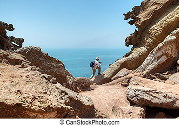 Tourist climbs the rock to make good shot of nature. -...