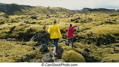 Aerial view of two woman walking on the lava field in Iceland. Tourists exploring the meadow covered moss, hiking.