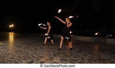 Fire show in the night. - Women twist fiery circles on a...