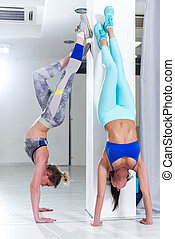 Two fit young Caucasian girls wearing sportswear performing...