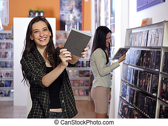 Happy women at the video rental store - Happy women choosing...