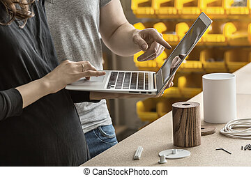Man and woman using laptop in workshop