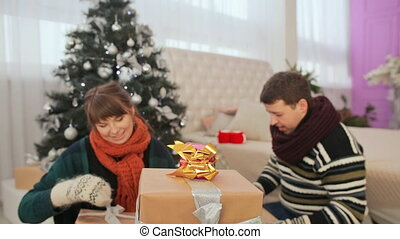 A guy and girls take gifts out of a pile of presents and open them up. Christmas theme.