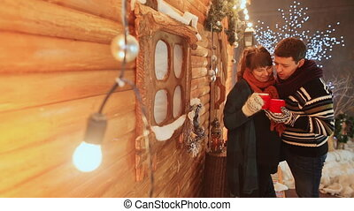 A couple in love sit on the background of a wooden fairy house warmed by cups with a hot drink. Christmas and New Year theme.