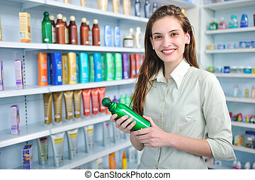woman at pharmacy buying shampoo - happy woman at pharmacy...