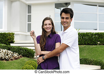 Couple buying a new house - Real estate: Couple showing keys...