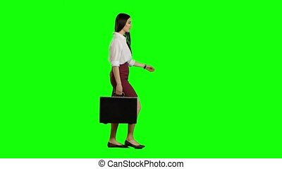 Asian girl looks on the road holding a briefcase in her...