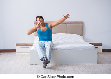 Young man waking up in bed