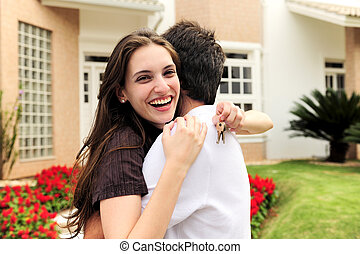 Couple standing outside new house - real estate: couple...