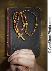 Hands with rosary and an old book - Female hands with rosary...