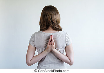 Woman with her hands laying together behind her back
