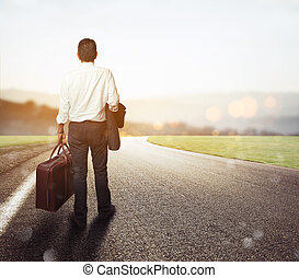 Businessman is on his way out - Man walks on a road with his...