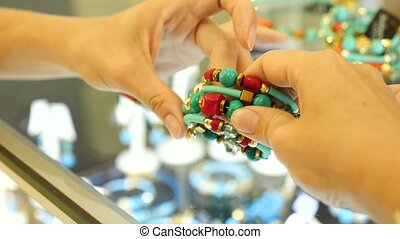close-up. Women's hands hold a bracelet of turquoise and...