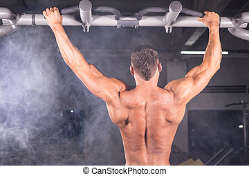 Strong man doing pull-ups on a bar in a gym. - Strong man...