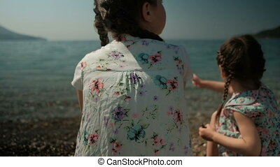 Two girls sit on the shore and throw stones into the water.