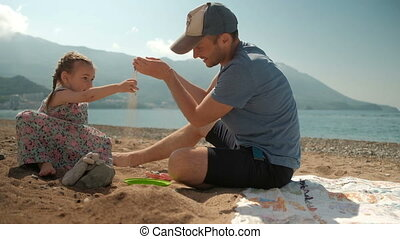 Daddy and daughter play gritfully on the seashore in sunny weather.