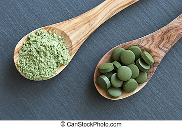Chlorella and young barley powder on two wooden spoons -...