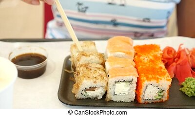 Caucasian woman eating sushi in a restaurant - Someone eats...