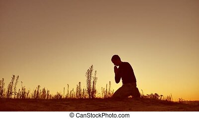 Silhouette illustration of a man praying outside at...