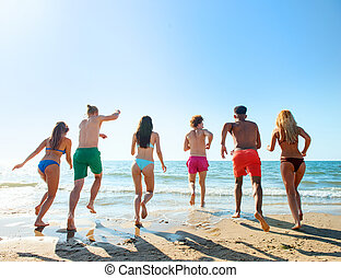 Group of friends run to the sea. Concept of summertime -...
