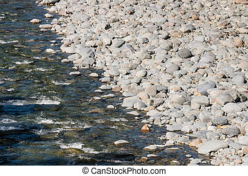 riverbed with grey pebbles and boulders - closeup of...