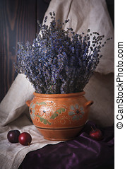 Still life with lavender in a clay jug and plums on the table.
