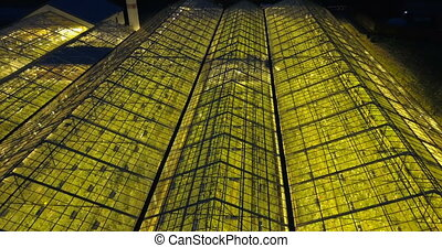 Aerial close up view of greenhouse with light inside. Copter...
