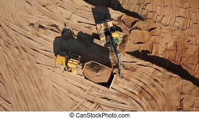 Excavator digs sand and loads it into a truck. Aerial top...