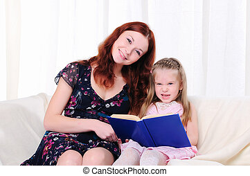 little girl and her mother read a book