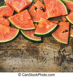 Juicy watermelon pieces over rustic wooden background,...