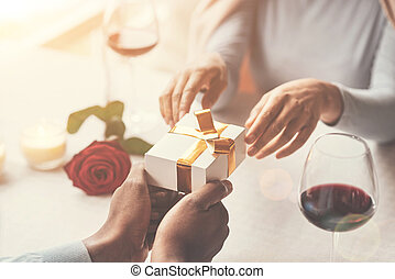 Beautiful small gift being in hands of a caring man -...