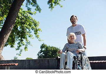 Radiant pleasant man taking senior lady out in the park