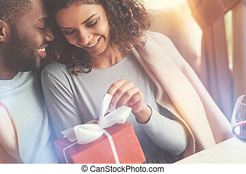 Beautiful happy woman unwrapping the present - What is...