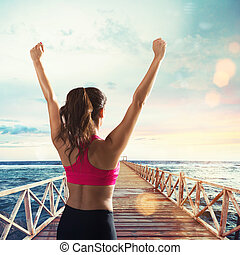 Stretching on a pier in front of sun - Girl stretches on a...