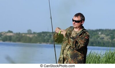 Man clings a bait to a fishing rod, he wants to catch fish -...