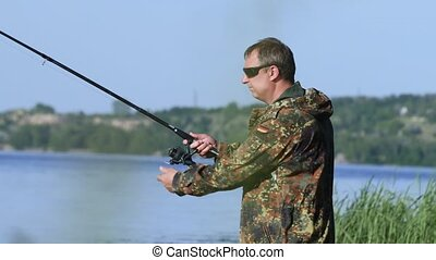 Fishing lover holds a rod in his hand and twists the reel...