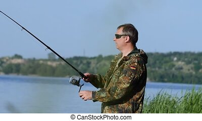 Fisherman holds a fishing rod in his hand and catches fish...