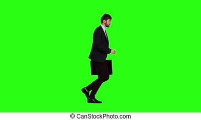 Man is running a briefcase in his hand, he rushes over it. Green screen. Slow motion