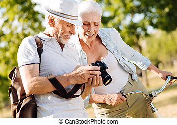 Positive delighted couple choosing best photos - Good...