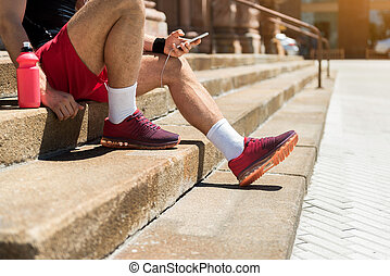 Youthful man in sportswear relaxing during exercise outdoor...