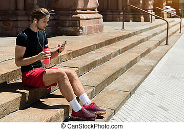 Serious youthful guy having break while training outdoor -...