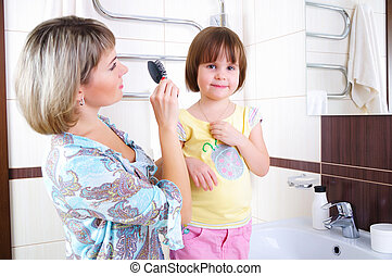 Mom combing hair of his little daughter in the bathroom