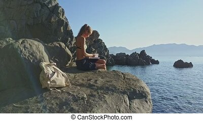 Side View Girl Reads Book on Rock by Ocean at Sunrise - side...