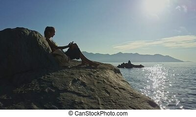 Girl Sits by Bag on Stone Listens to Music against Ocean -...