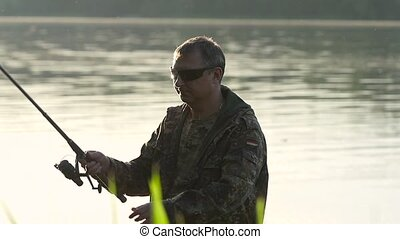 Man clings a bait to a fishing rod, he wants to catch fish....