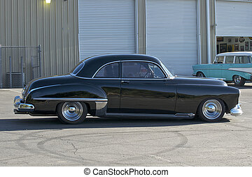 A lowered 1949 coupe is parked in front of a hot rod shop