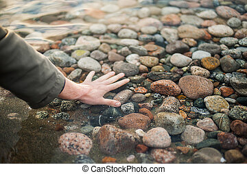 Hand in the clear water of the lake. Seen stones on the bottom