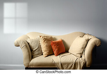 Sofa - Elegant sofa with pillows against bare white wall