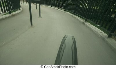 POV of a spinning rear bicycle wheel, cycling up the city...