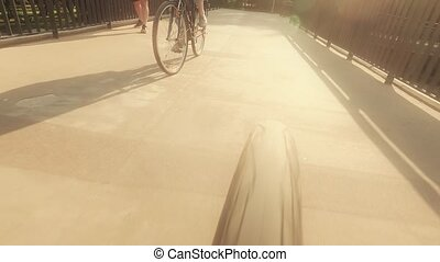 POV of a spinning rear bicycle wheel, cycling down the city...